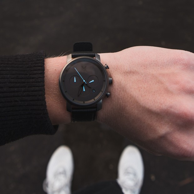gunmetal and black leather watch on a mans wrist