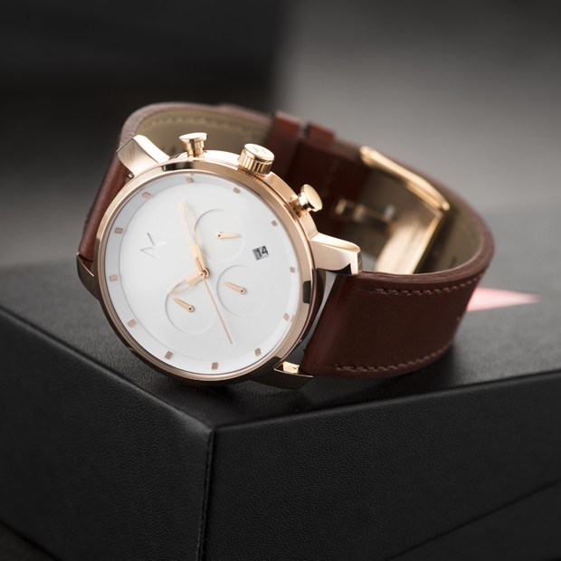 rose gold and tan leather watch propped up on a box