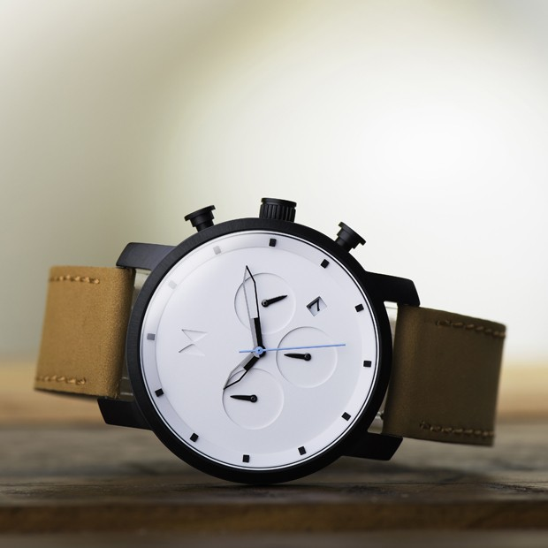 white black and tan leather watch on a wood surface