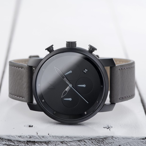 black and grey leather watch on a wood surface