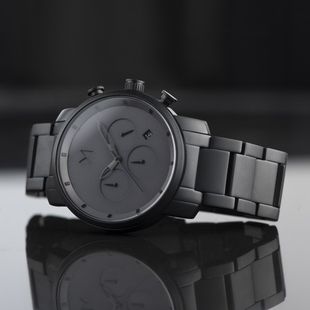grey and black link watch on a black reflective background