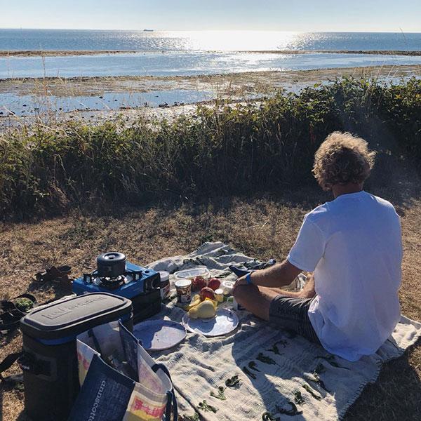 Male sat on picnic blanket.