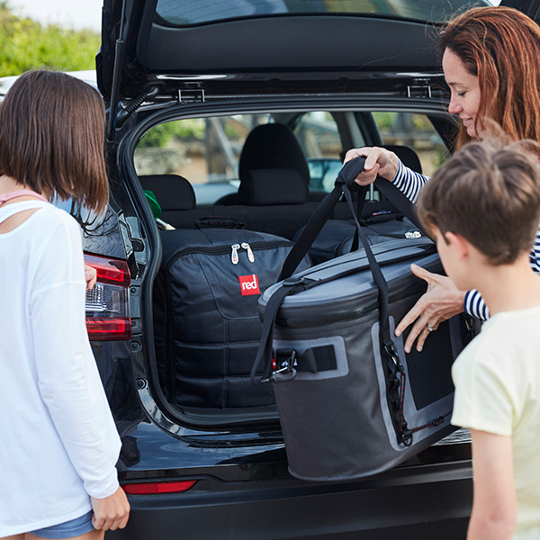 Mother unloads car carrying cool bag