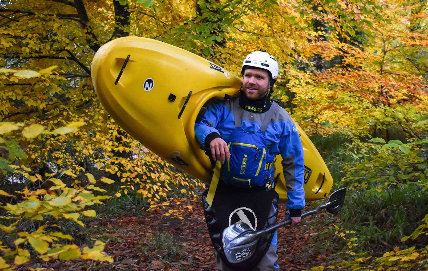 A Man Carrying A Kayak Over His Shoulder