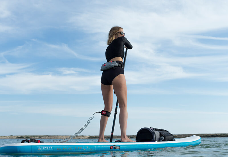 A Woman On A SUP Wearing The Red Original Airbelt PFD Around Her Waist