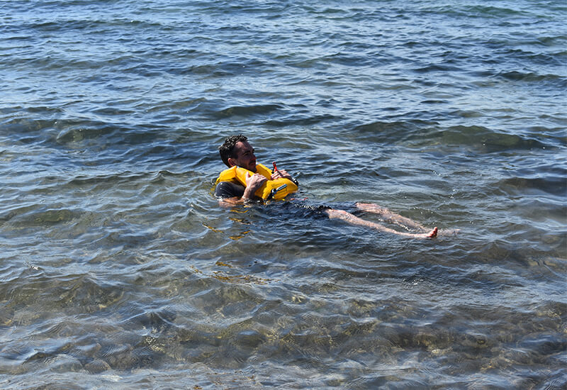 A Man Floating In The Sea With An Inflated Red Original Airbelt PFD