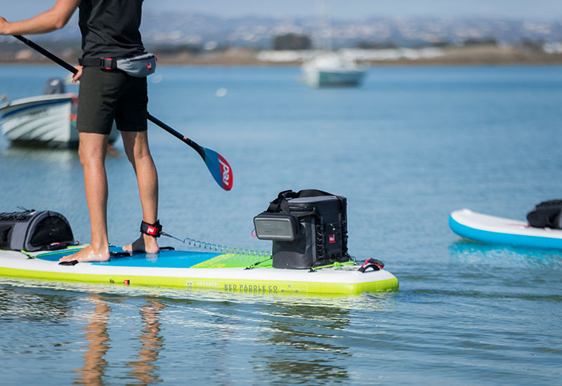 The Red Original Waterproof Pouch & Cooler Bag On a Red Paddle Board