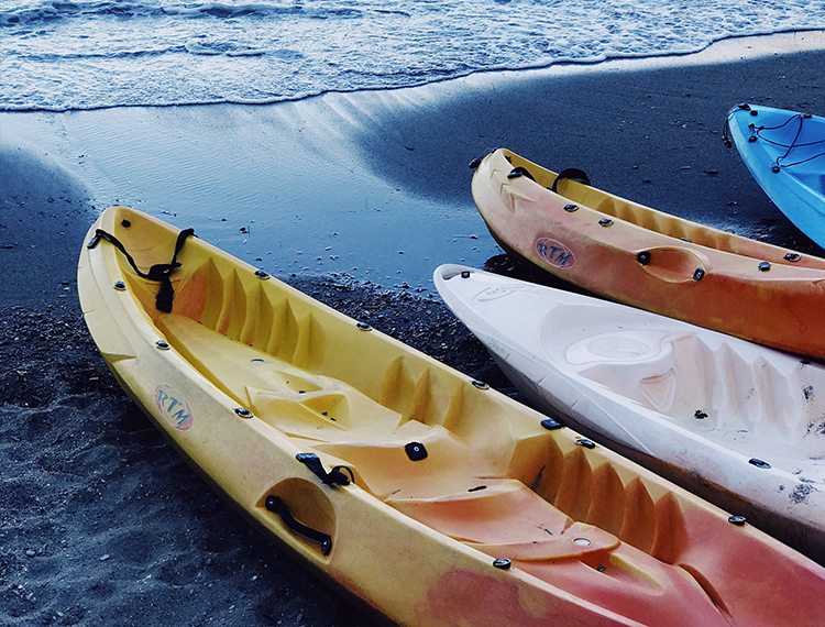 Sea Kayaks Sat On The Beach Next To The Sea
