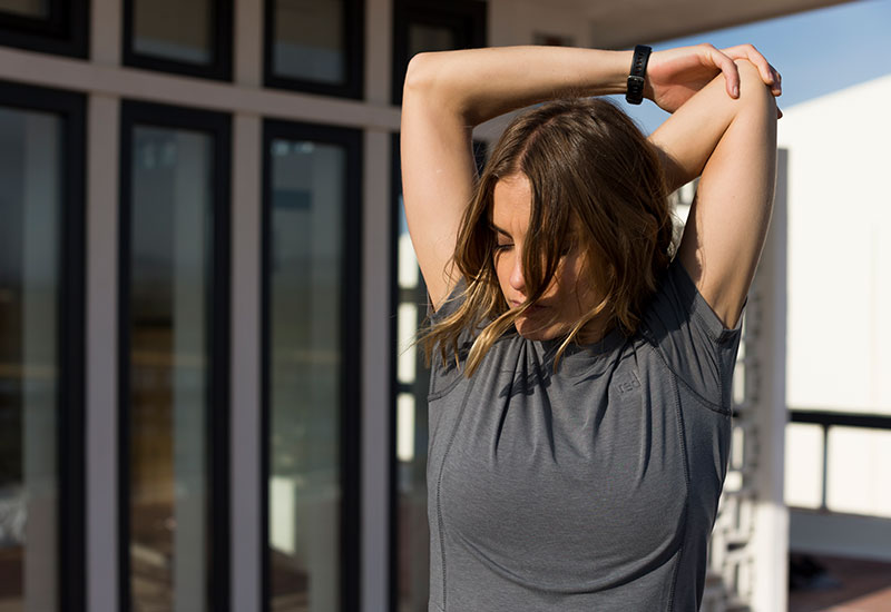 woman stretching whilst wearing the Red Original Women's Performance T Shirt