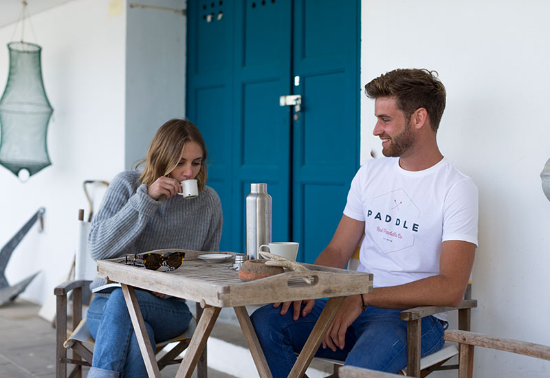 couple enjoying a coffee wearing Red Original Paddle On white t-shirt