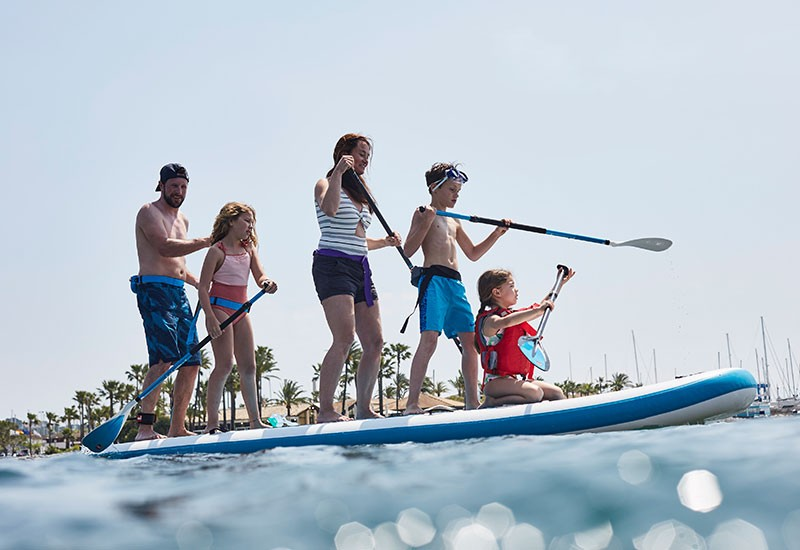family paddle boarding at sea on holiday