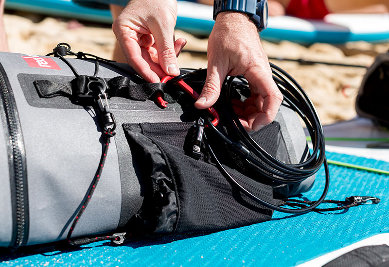 attaching a Red Original board lock onto the side of a deck bag on a sup