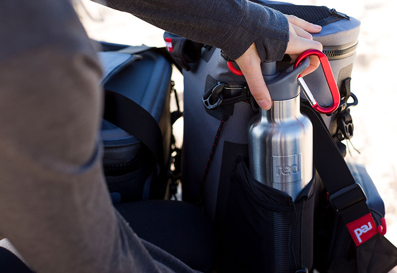 Woman loading the Red Original Insulated Drinks bottle into the side pocket of a Red Original Deck bag