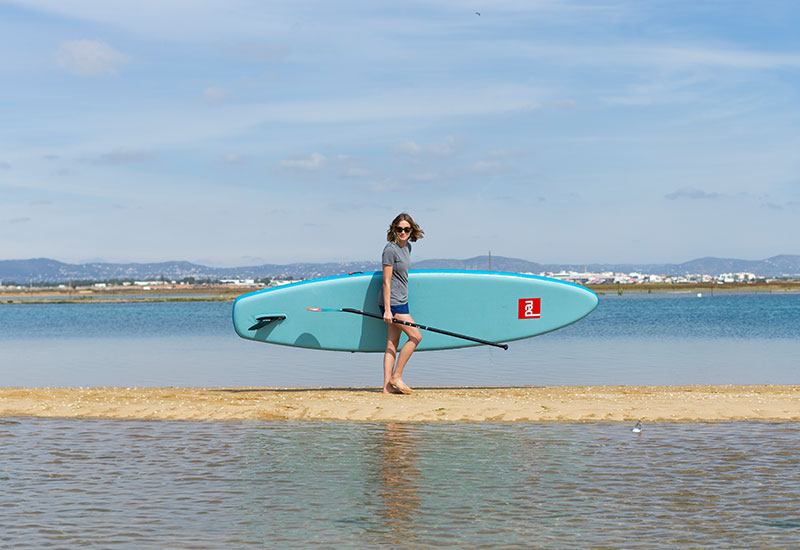 female carrying a SUP whilst wearing the Red Original Women's Performance T Shirt