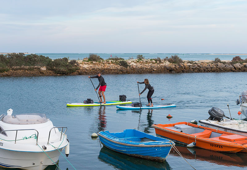 Couple paddle boarding in Portugal