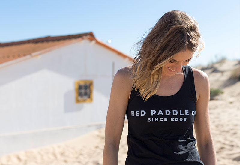 Woman on a beach wearing the Red Original Since 2008 vest