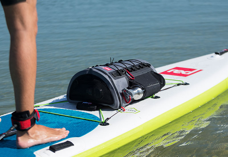 Man paddle boarding with a Red Original Insulated Drinks bottle in a deck bag