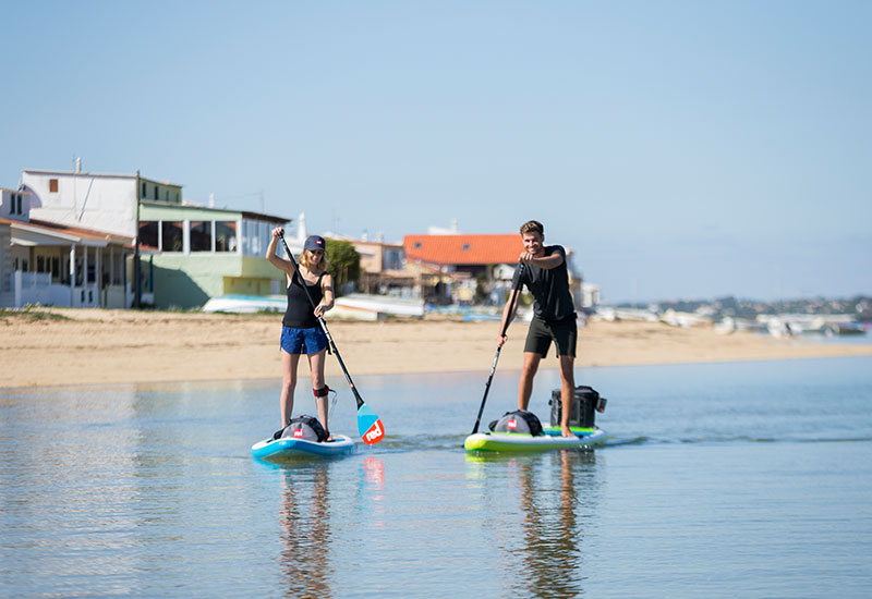 couple paddle boarding with deck bags