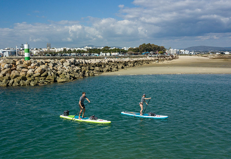 Couple paddle boarding wearing Red Original Performance T Shirts