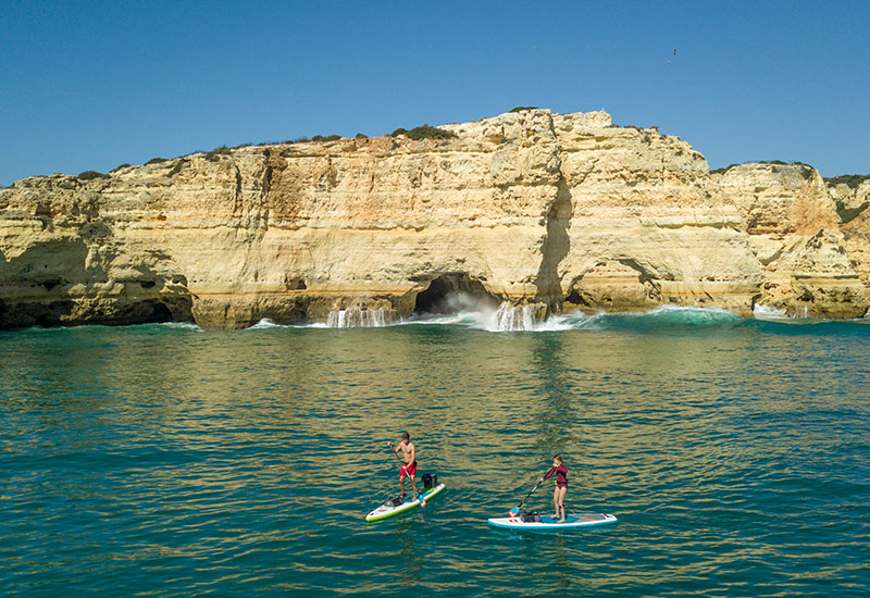 couple out on a paddle boarding adventure with Red Original deck bags on their sups
