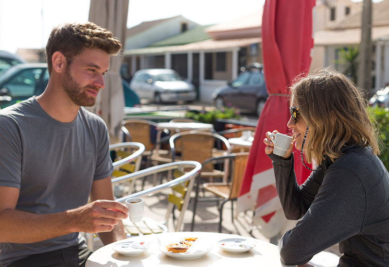 Couple drinking coffee with their boards locked up in the background with Red Original board lock
