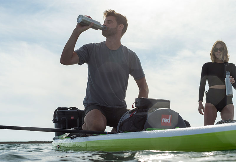 Man drinking from a Red Original Insulated Drinks bottle whilst resting on a stand up paddle board