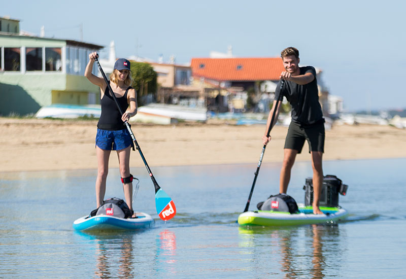 couple stand up paddle boarding on water