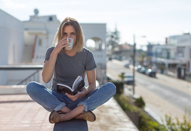 female drinking coffee whilst wearing the Red Original Women's Performance T Shirt