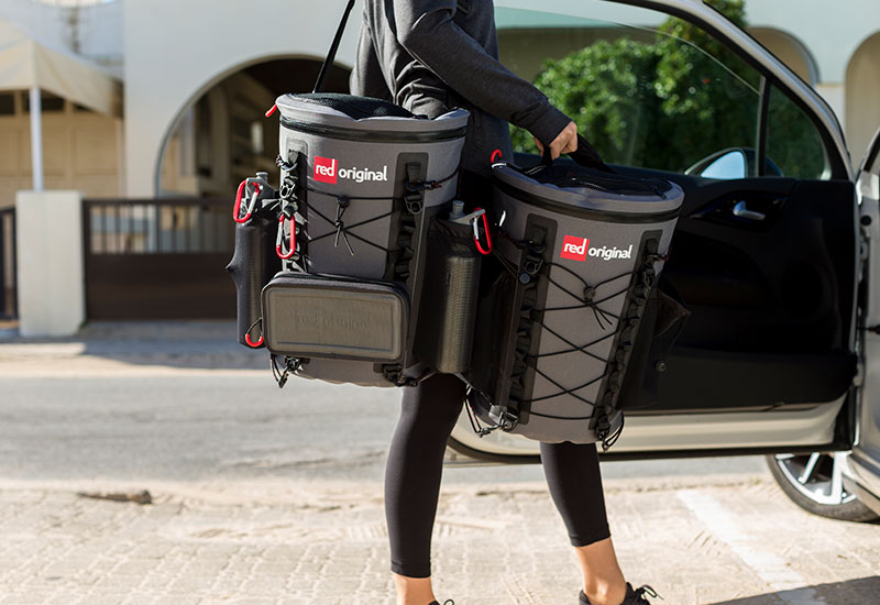 woman loading Red Original deck bags into car after paddle boarding