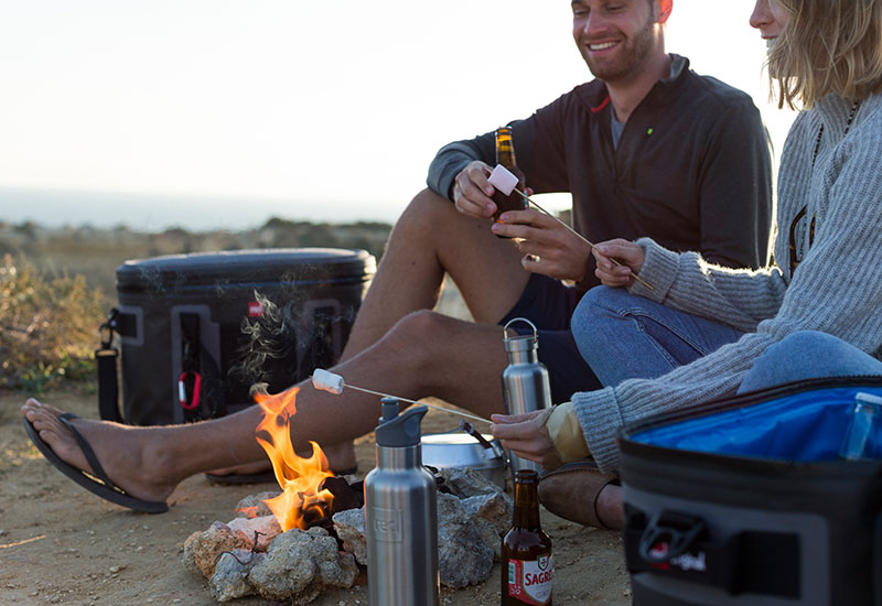 Couple relaxing by a bonfire with their Red Original Insulated Drinks bottles
