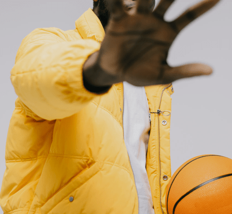 Man in yellow jacket with basketball