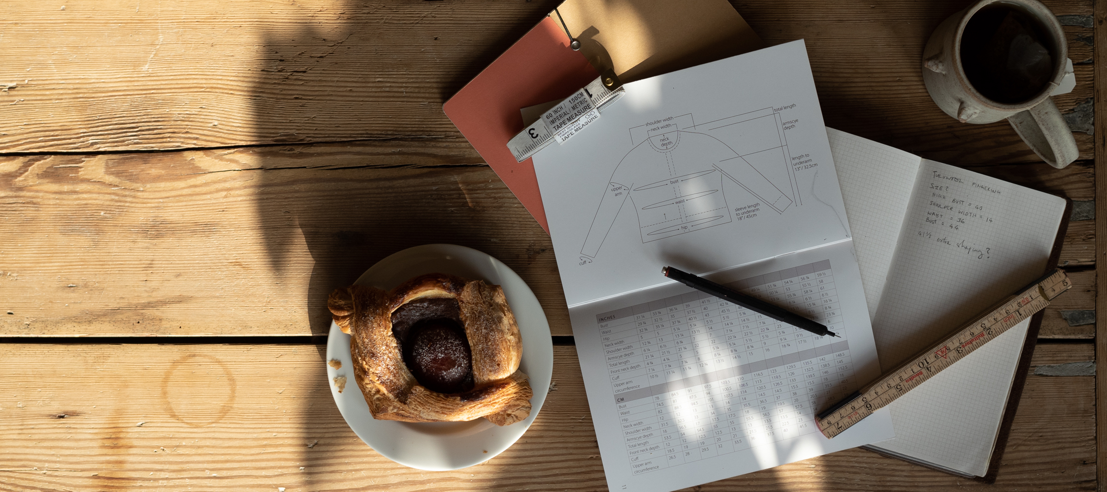 a pastry, coffee, knitting pattern, notebooks, pencil and measuring tape