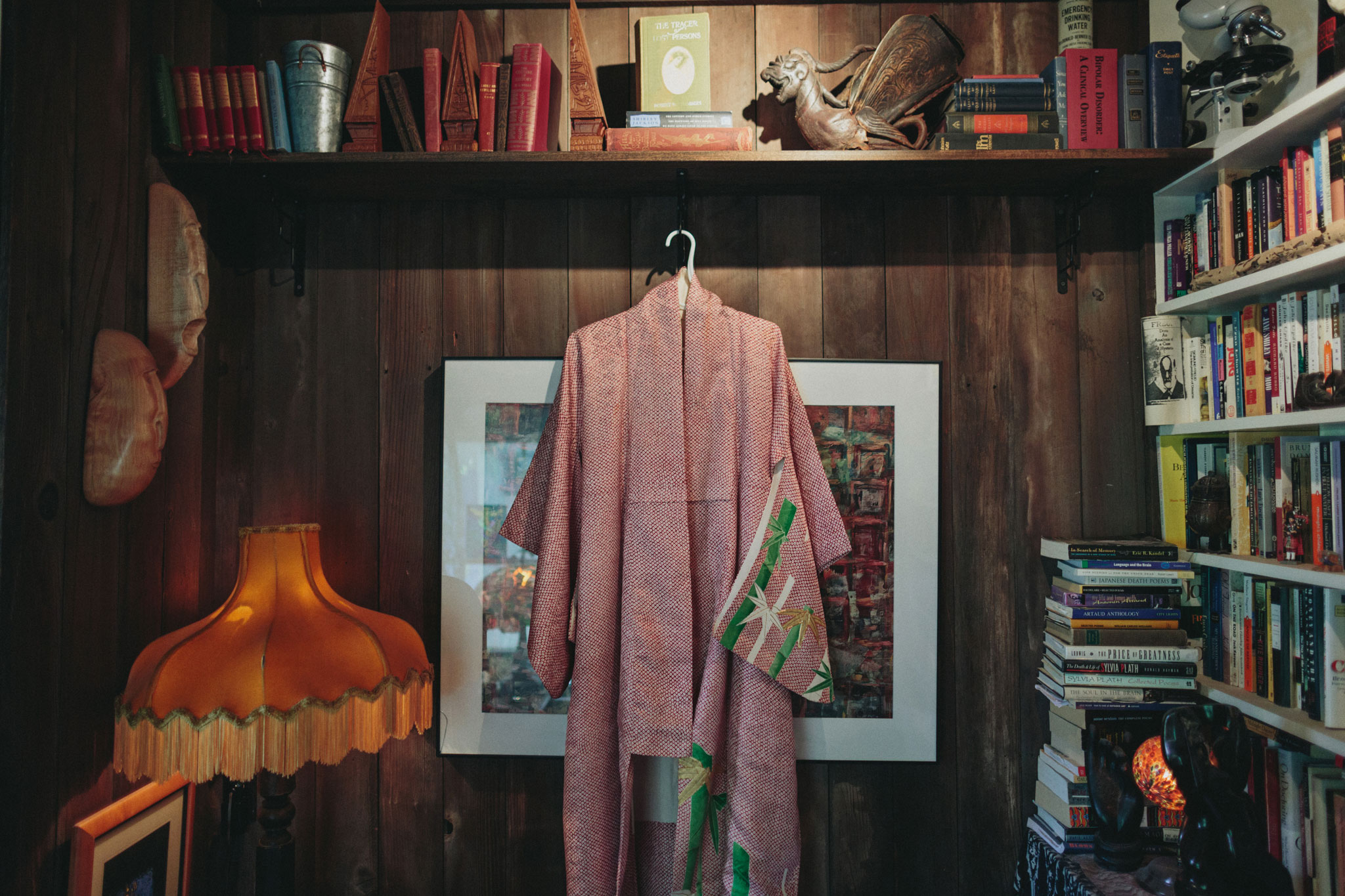 Pink and green kimono and haori hanging in a woodpanelled room with bookshelves